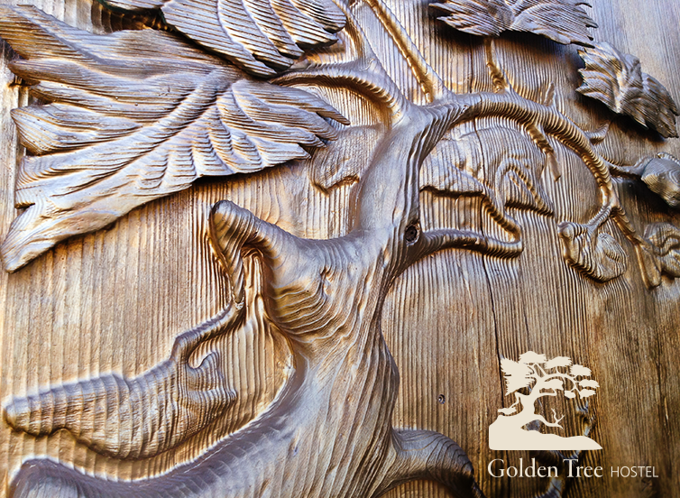 Golden wood carving of a tree that inspired the name and logo design of Golden Tree Hostel.